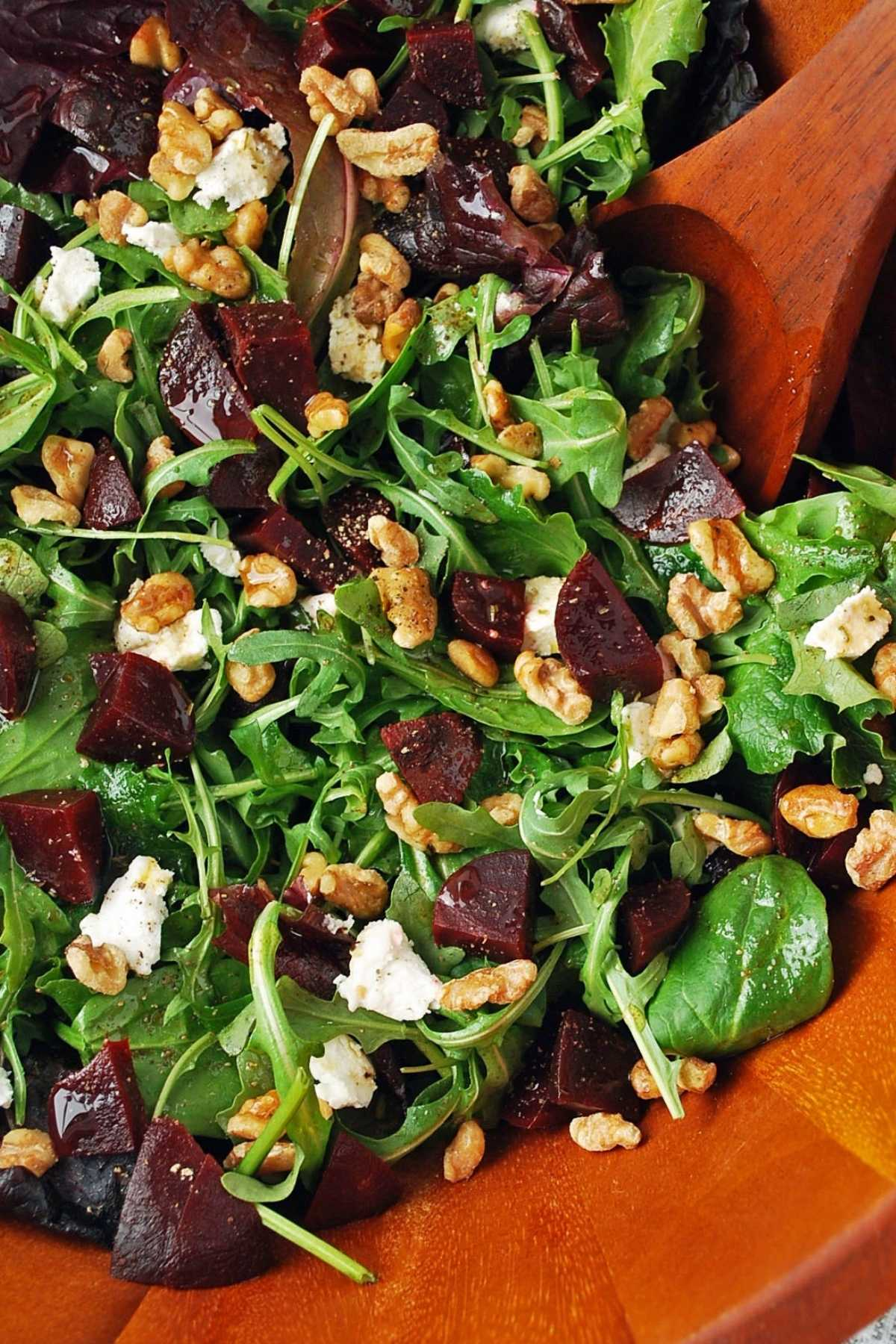 close up of a mixed green salad with beets, goat cheese, walnuts, and dressing being tossed together with a wooden spoon
