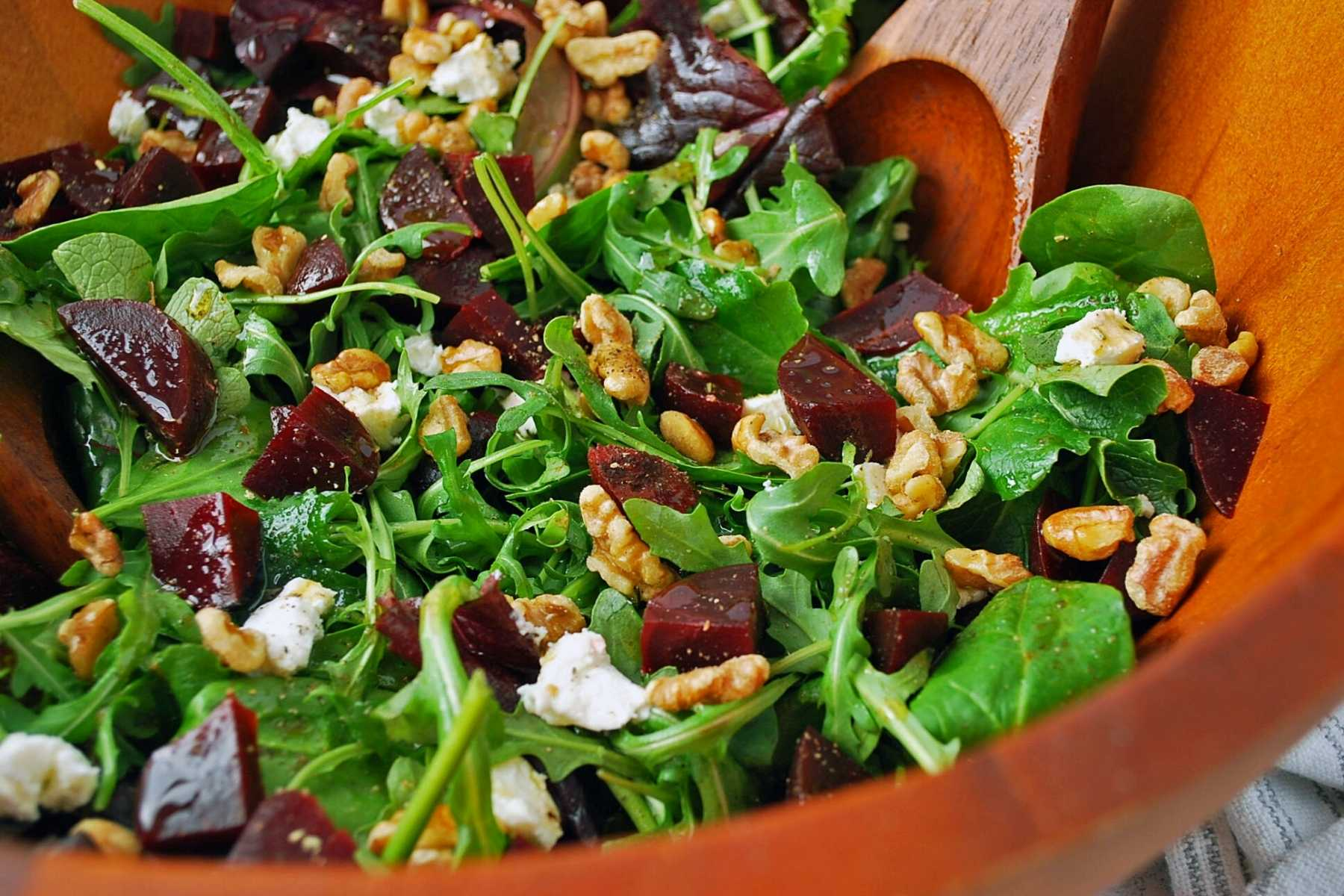Side view of a serving bowl of beet salad with greens, goat cheese, walnuts, and dressing