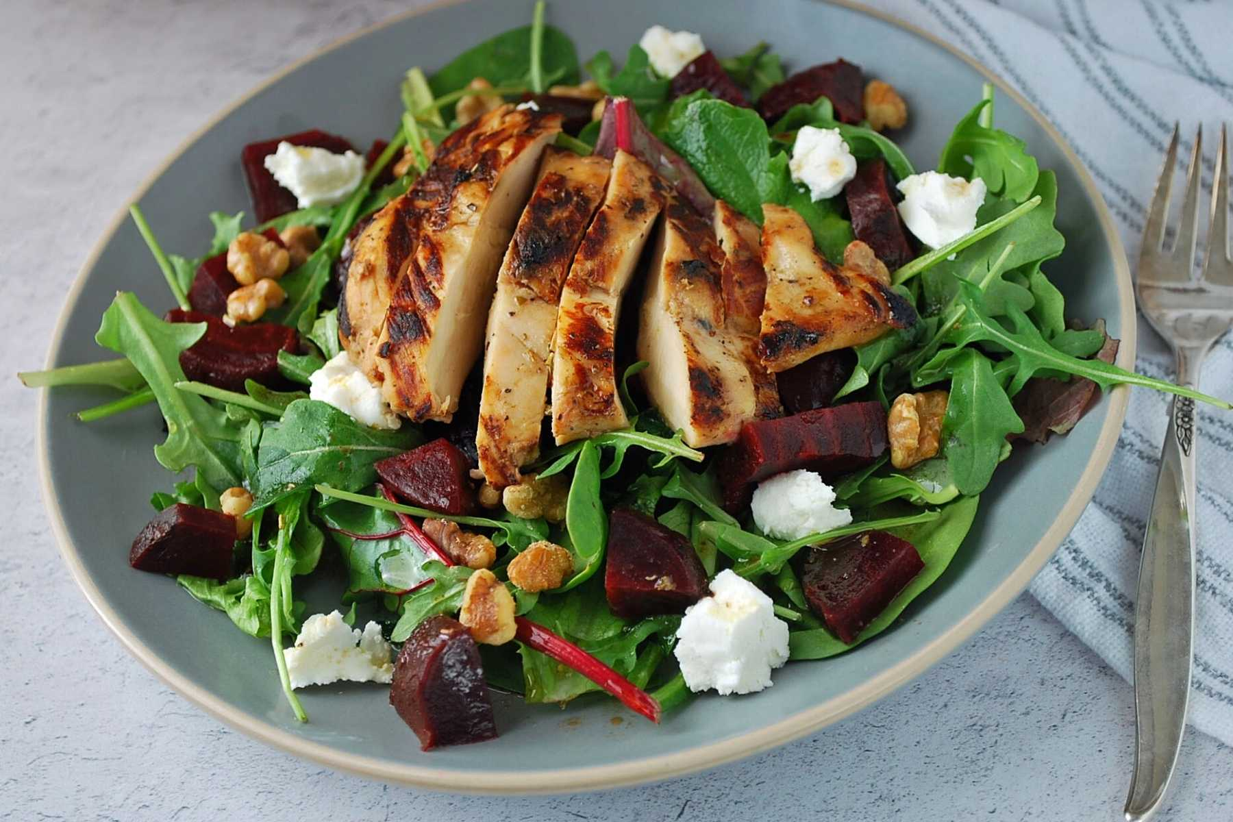A salad plate with mixed greens, goat cheese, beets, walnuts, and grilled chicken on top