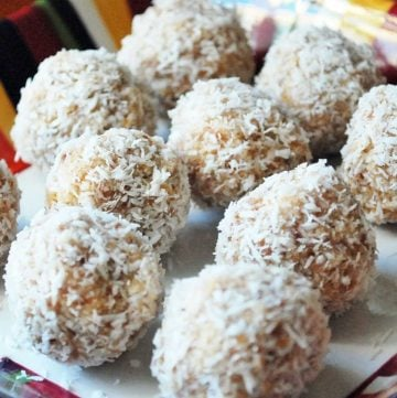 energy balls covered in shredded coconut on a plate