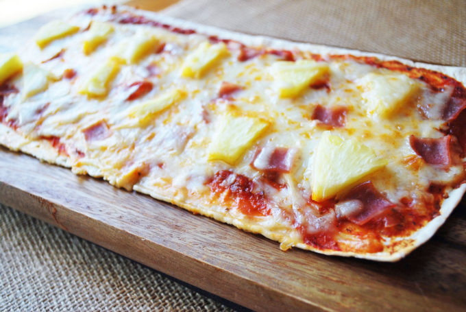 Rustic white flatbread Hawaiian pizza with ham and pineapple