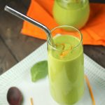 green smoothie in a glass on a white plate with spinach leaves and orange peel around it