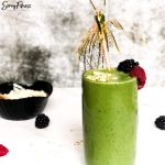 spinach smoothie in a glass with fruit and a fun sparkly pick on top