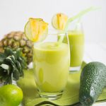 two pineapple avocado smoothies in a glass with an avocado and fresh pineapple next to the glasses