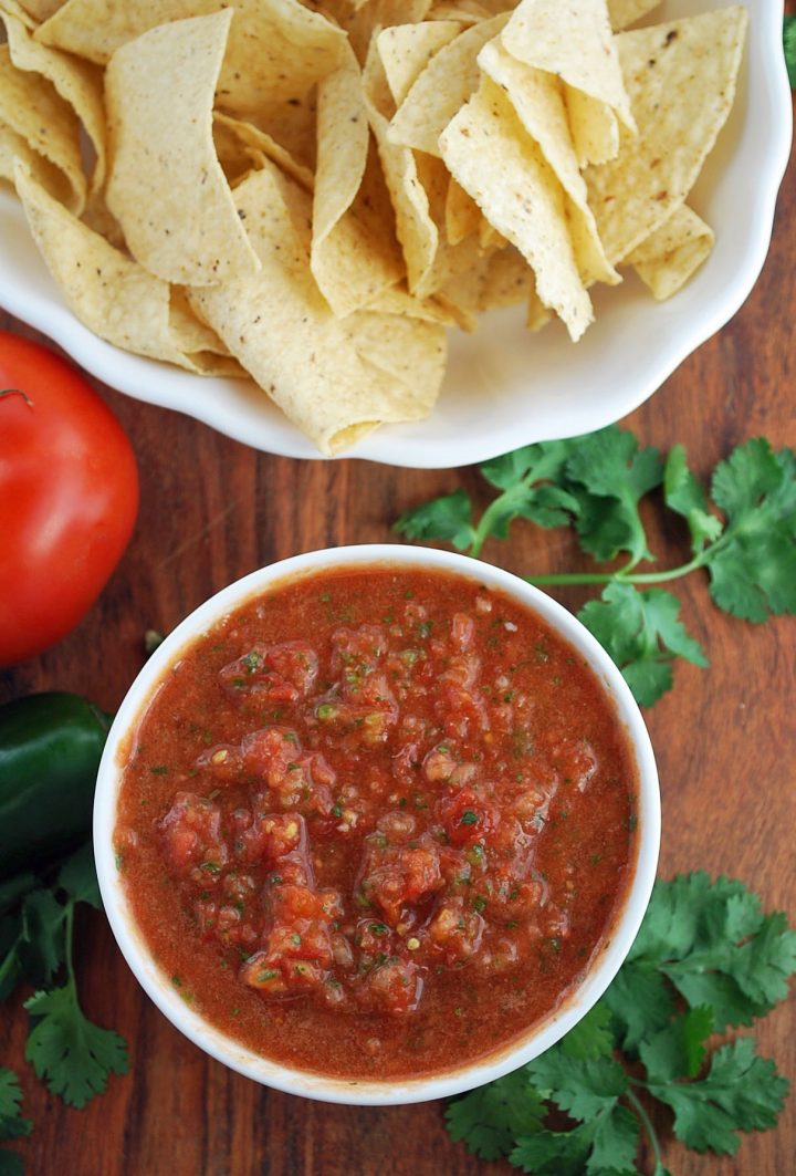 fresh salsa in a bowl surrounded by fresh cilantro and chips