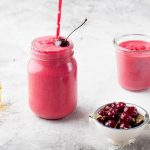 cherry pear spinach smoothie in a glass with cherries in a bowl in front