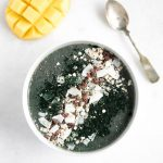 spirulina smoothie bowl with a sliced mango next to it and a spoon