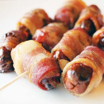 cooked bacon wrapped dates with a toothpick in one of them for serving