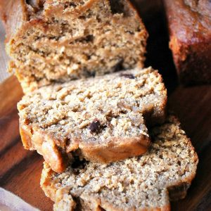 close up of a sliced loaf of banana bread with chocolate chips on a cutting board
