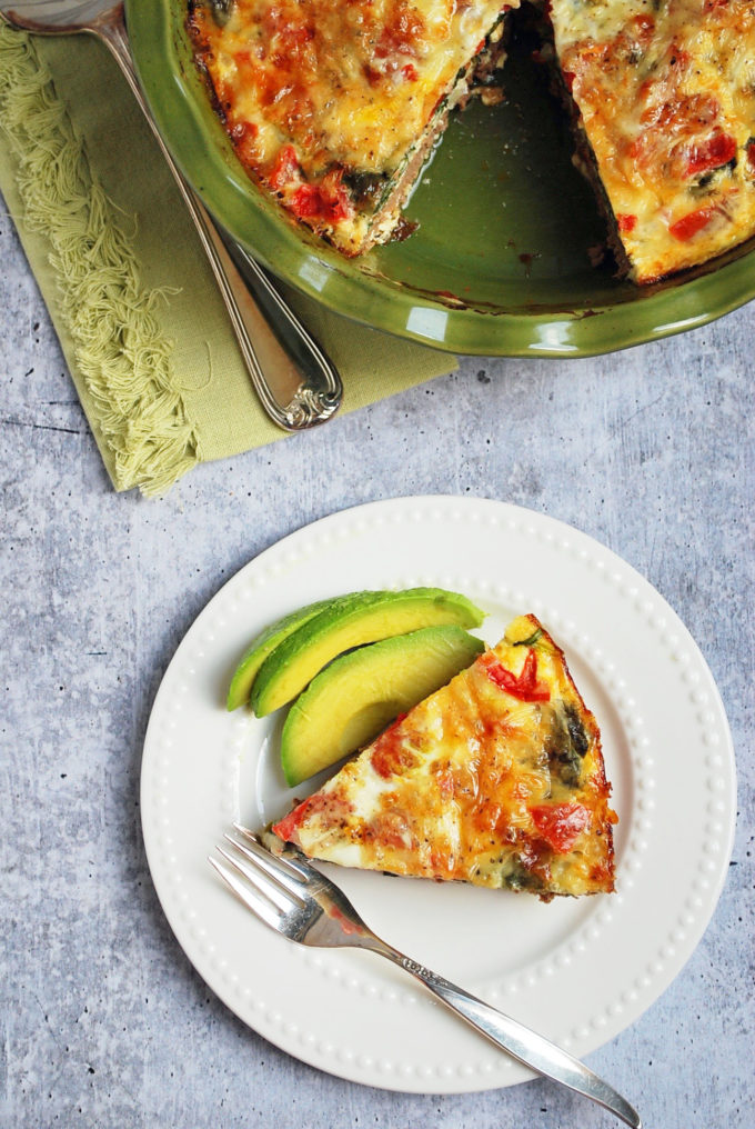 a slice cheeseburger quiche, avocado slices, and a fork on a plate