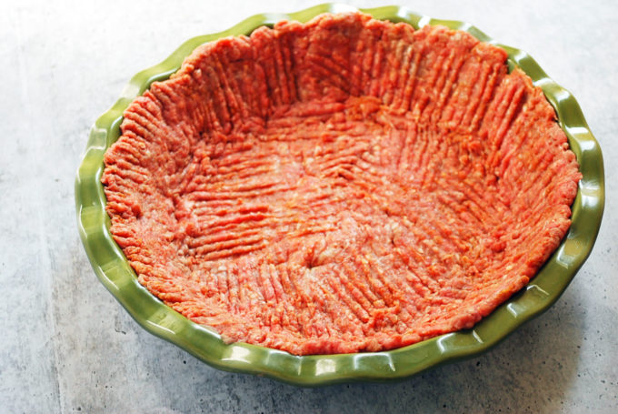 ground beef spread out in a pie plate