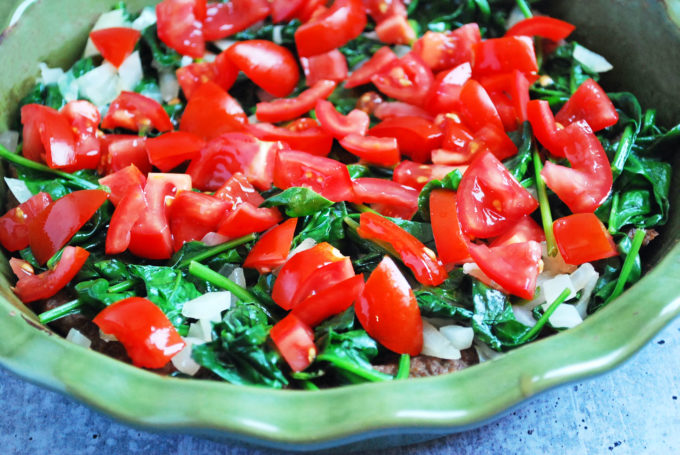 tomatoes, onions, and spinach in a pie plate