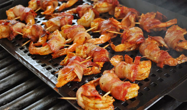 Bacon-wrapped adobo shrimp cooking on the grill