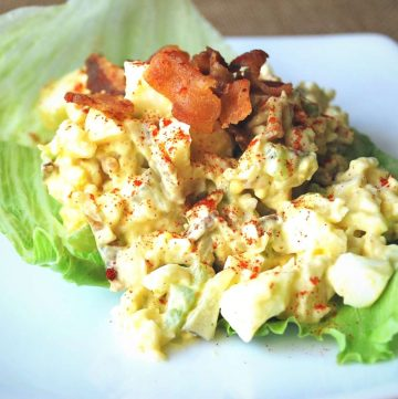 egg salad on a lettuce leaf topped with crumbled bacon