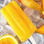 Mango orange popsicle on ice with fruit slices