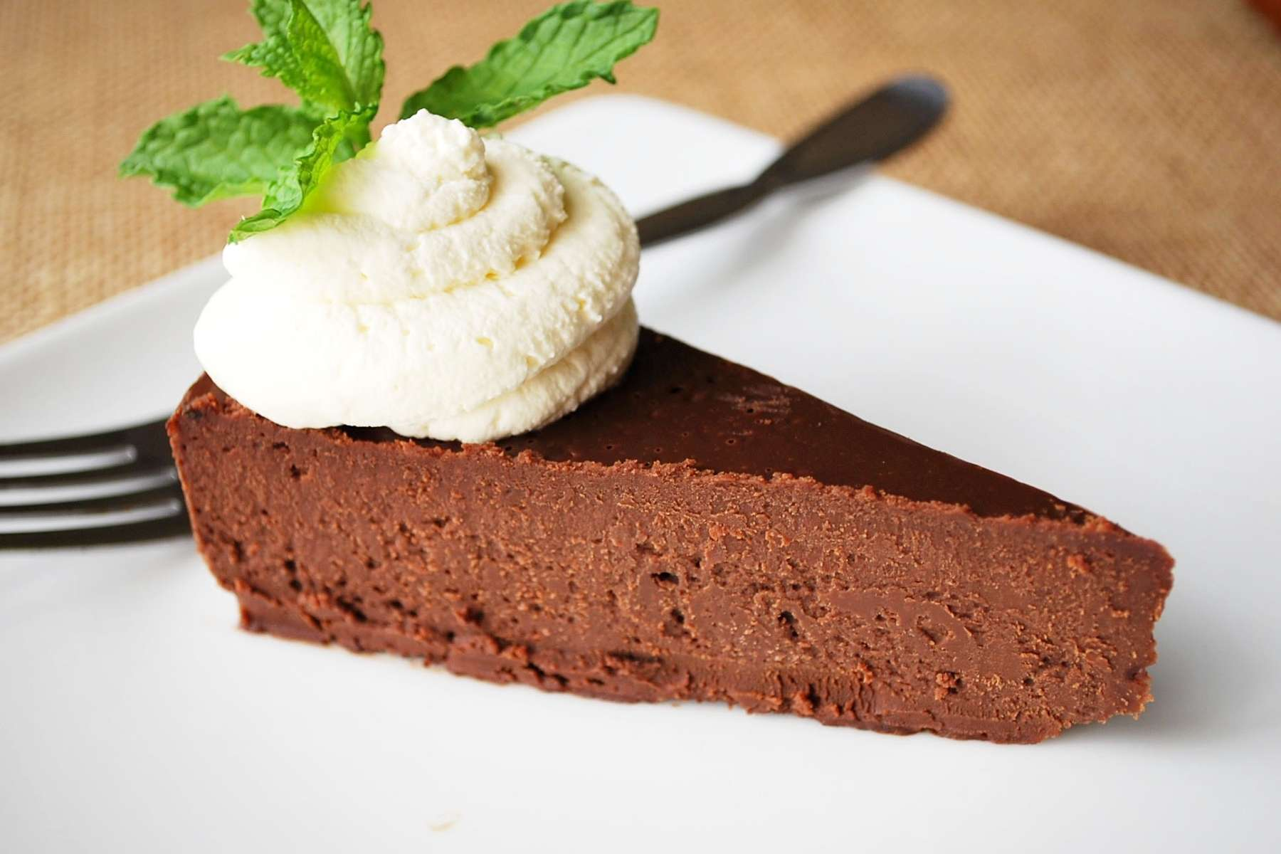 slice of chocolate cake topped with whipped cream and mint on a plate with a fork