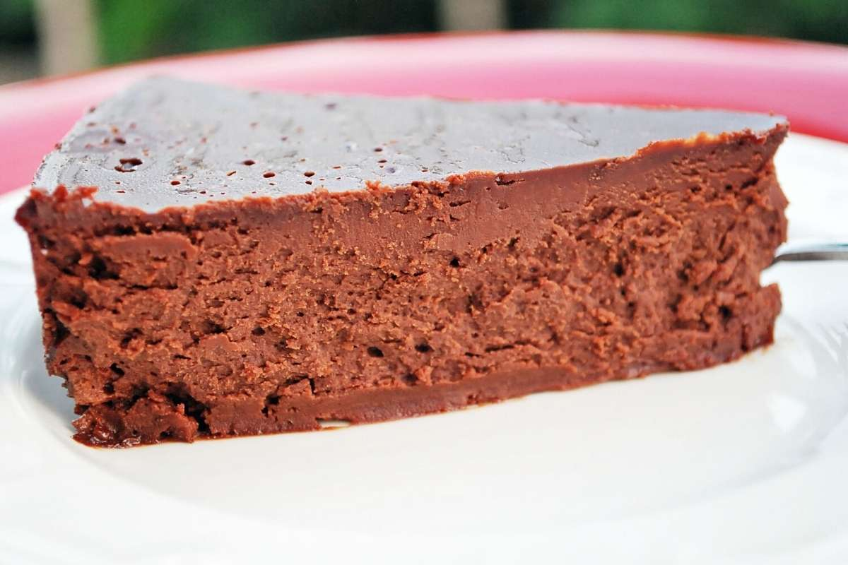 close up side view of a slice of flourless chocolate cake on a plate