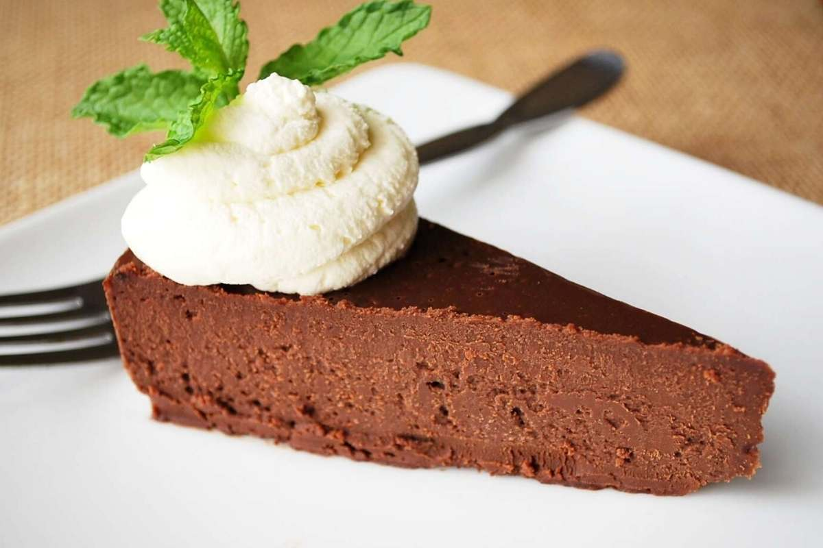 a slice of Paleo flourless chocolate torte on a plate topped with whipped cream and a sprig of mint
