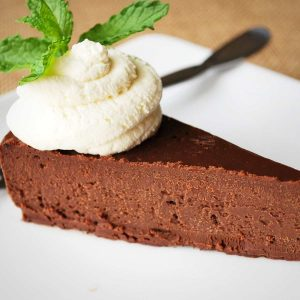 slice of dense chocolate cake on a white plate with a whipped cream and mint garnish