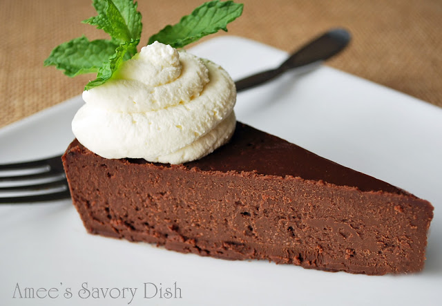 a slice of flourless chocolate torte topped with a dollop of whipped cream