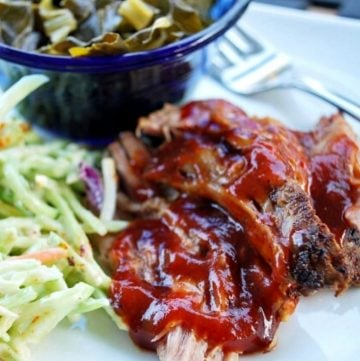 close-up photo of pulled pork barbecue on a plate with slaw and collard greens