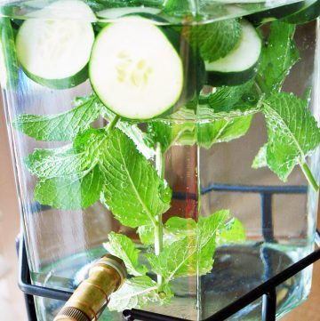 water in a drink dispenser with fresh cucumber and mint