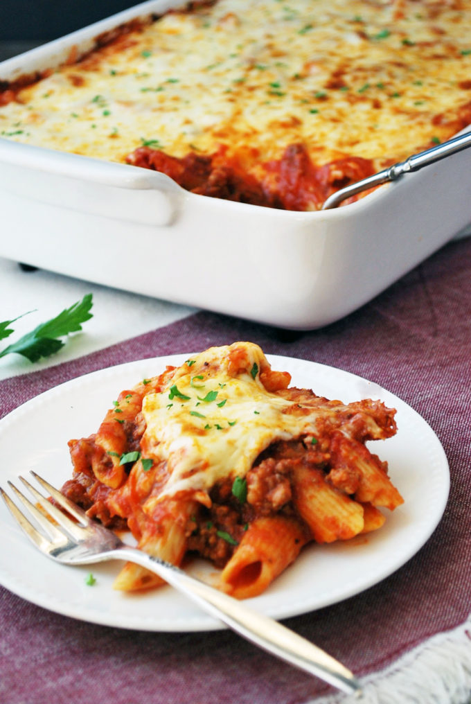 Serving of baked mostaccioli on a plate with casserole in background
