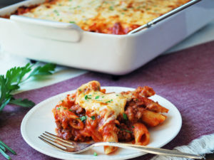 serving of baked mostaccioli with a fork and pan in the background