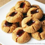 Gluten-free peanut butter and jelly thumbprint cookies are delicious, soft peanut butter cookies with fresh fruit preserves in the center.