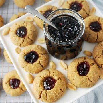 overhead photo of peanut butter thumbprint cookies with a jar of jam in the middle and peanuts sprinkled around the platter