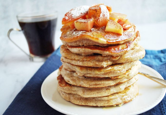 Stack of apple cinnamon protein pancakes with a cup of coffee