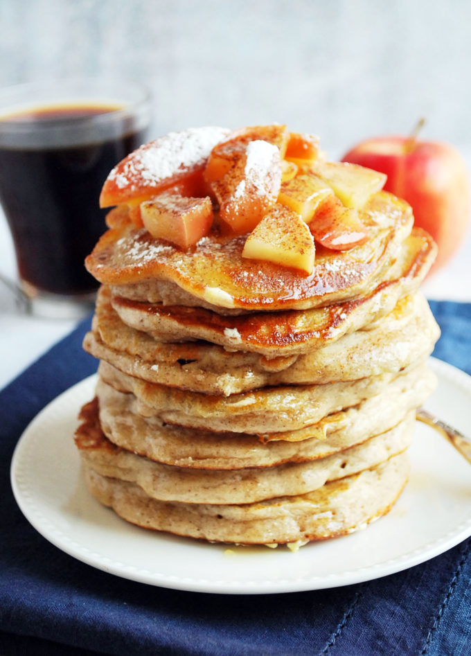 Stack of apple cinnamon protein pancakes topped with chopped apples, butter and dripping with maple syrup