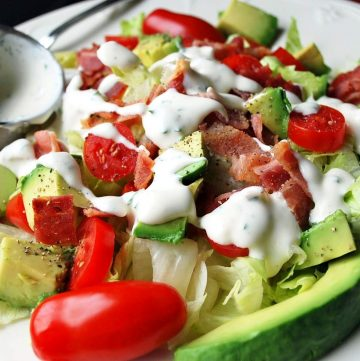 close up of a salad with tomatoes, avocados, bacon and ranch in a bowl