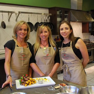 Three women in aprons standing behind a food prep counter