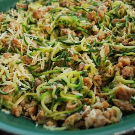sausage parmesan zucchini pasta on a green plate