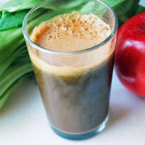 green power juice in a glass with an apple and bok choy