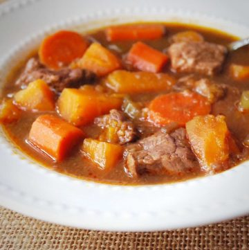 close up of a bowl of beef stew with sweet potatoes and carrots with a spoon