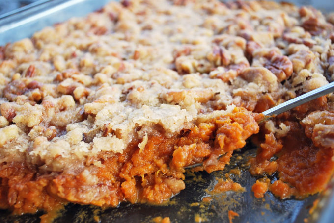 A close up of a spoonful of sweet potato casserole in a baking dish