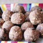 A recipe for chocolate peanut butter protein balls with dates made with dark chocolate chips, oats, coconut, dates, peanut butter, healthy seeds, coconut oil and honey.