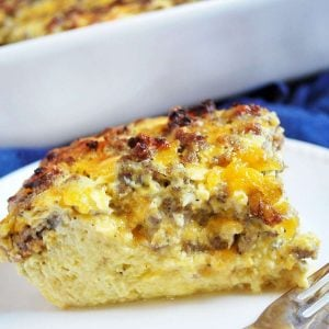 Overnight breakfast casserole with sausage and egg sliced on a plate with a fork next to it