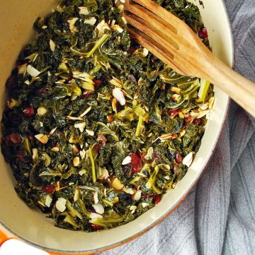 braised kale with almonds and cranberries in a pot with a spoon