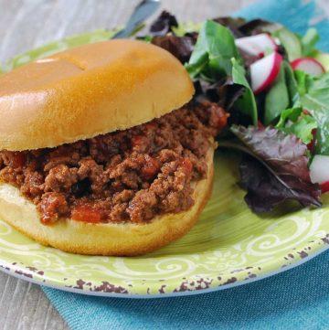 a sloppy joe sandwich with a garden salad on a green plate on top of a blue napkin