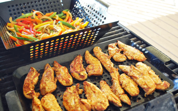 chicken tenders and vegetables on a grill