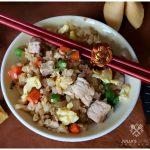 pork fried cauliflower rice in a bowl with chopsticks on top