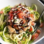 zucchini noodles in a bowl topped with chicken with a brushetta topping