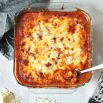 casserole topped with tomato sauce and cheese in a pan with a serving spoon