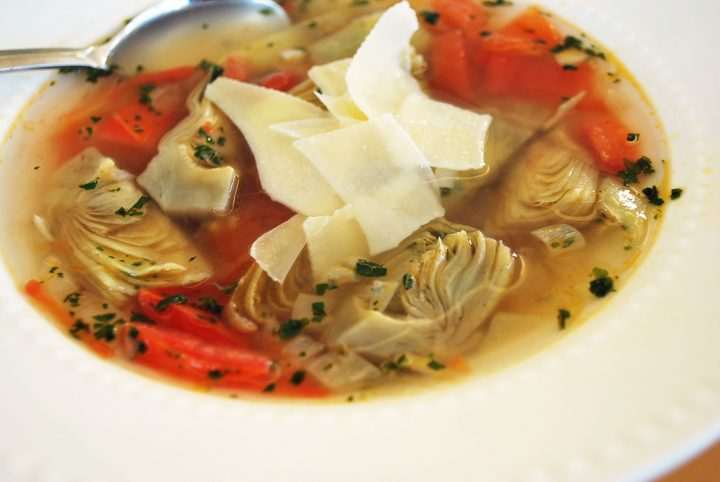 bowl of artichoke soup with shredded parm on top
