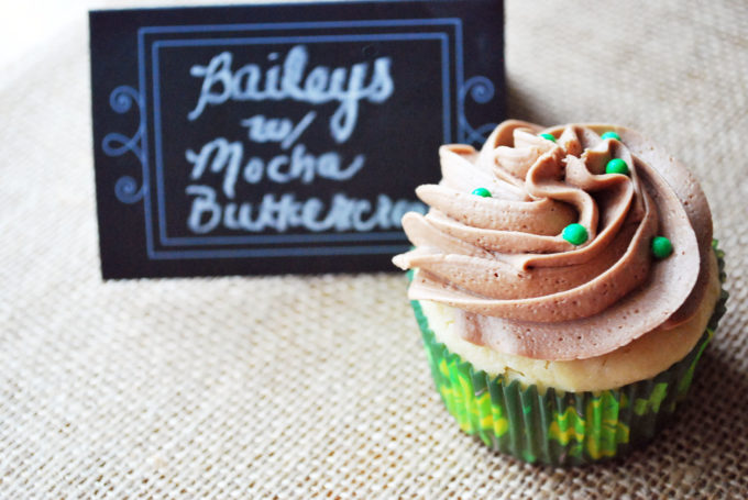 A Baileys cupcake with green sprinkles
