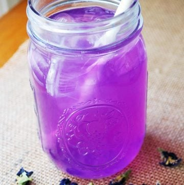 glass of purple lemonade made from dried butterfly pea blossoms