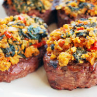Four grilled steaks topped with a Mediterranean topping blend of spinach, feta and sun-dried tomato pesto